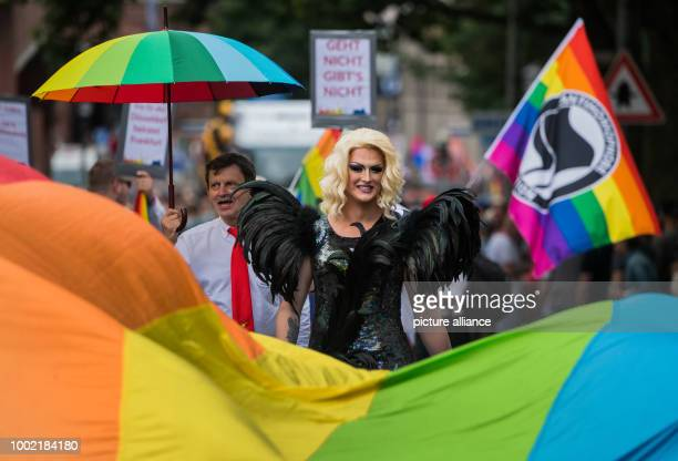 A participant wearing a black outfit walks behind rainbow coloured flag in Frankfurt am Main Germany 15 July 2017 Thousands of lesbians and gays take...