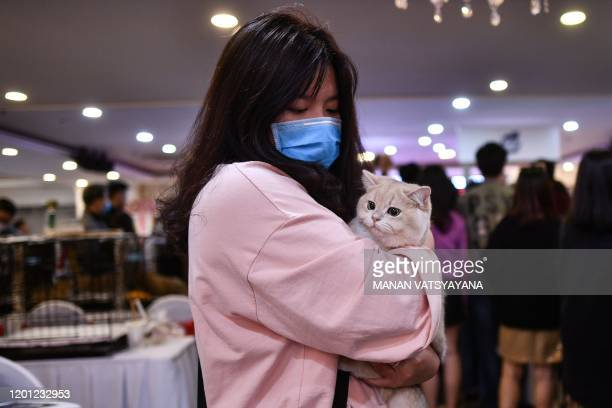 A participant wearing a protective facemask carries her cat during Vietnam's first national cat show in Hanoi on February 16 2020 amid concerns of...