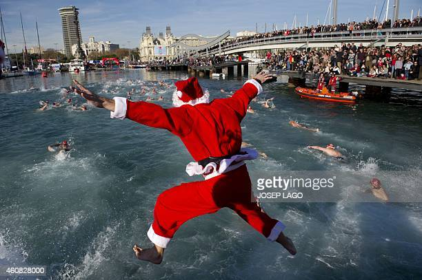 A participant wearing a Santa Clause costume jumps into the water during the105th edition of the Copa Nadal in Barcelona's Port Vell on December 25...