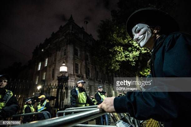 A participant wearing the Guy Fawkes mask seen facing the police as he stands in front of Downing street Demonstrators attend the Annual Million Mask...