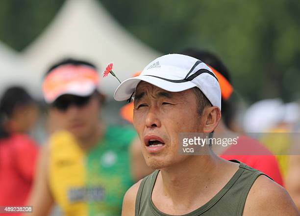 A participant wearing the popular plastic grass hairpins competes during the 2015 Beijing Marathon on September 20 2015 in Beijing China