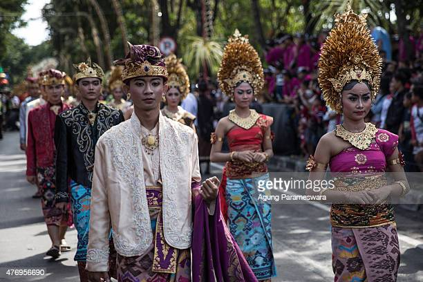 Participant wearing traditional Balinese wedding costumes walk during a parade of the opening 37th Bali International Arts Festival on June 13 2015...