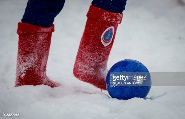 TOPSHOT A participant wearing Valenki traditional Russian felt boots bearing the 2018 FIFA World Cup logo takes part in a friendly football match...