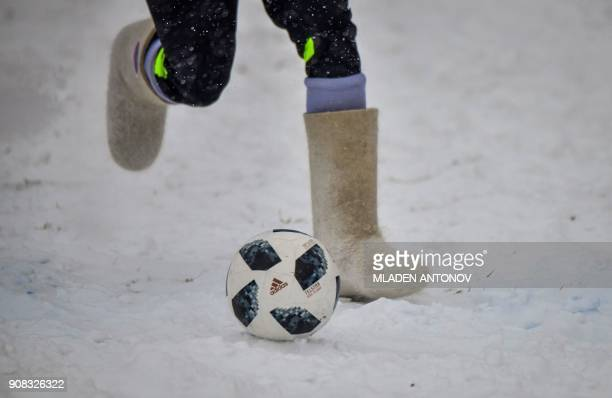 A participant wearing Valenki traditional Russian felt boots bearing the 2018 FIFA World Cup logo runs with the ball during a friendly football match...