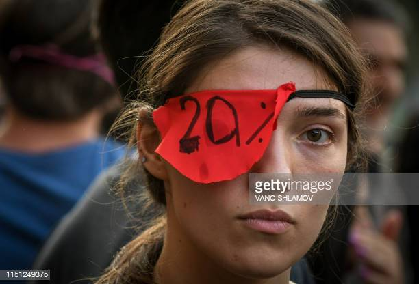 A participant wears a red eye patch with 20% inscription during a rally in front of the Parliament building in Tbilisi on June 21 2019 The head of...