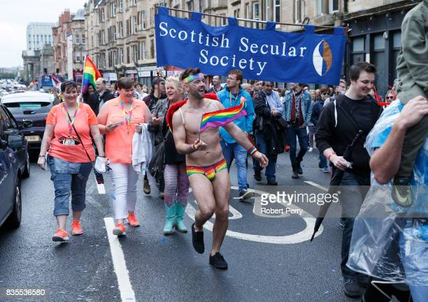 A participant wears rainbow pants and waves a flag during the Glasgow Pride march on August 19 2017 in Glasgow Scotland The largest festival of LGBTI...