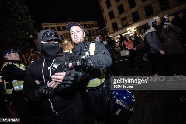 A participant with a mask seen being arrested by the police Demonstrators attend the Annual Million Mask March bonfire night protest advertised as a...