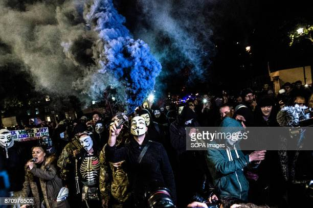 Participant with the Guy Fawkes mask seen releasing some smoke during the march Demonstrators attend the Annual Million Mask March bonfire night...