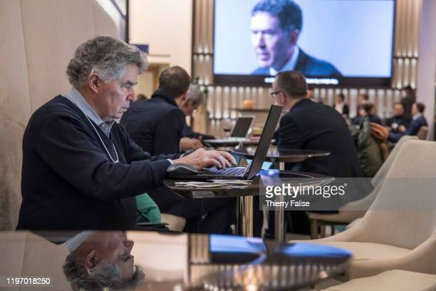 A participant works on his computer in a public lounge at the 50th World Economic Forum in Davos