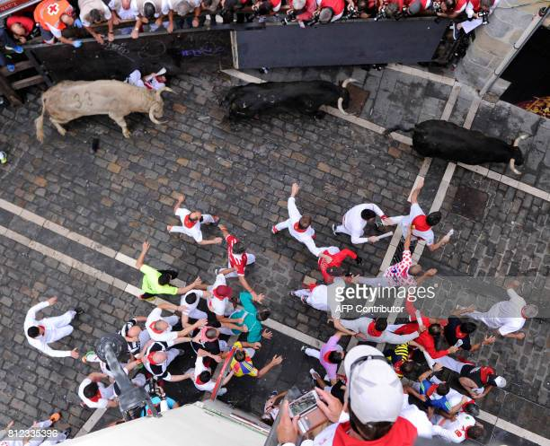 Participants and Jandilla's fighting bulls turn Mercaderes curve during the fifth bull run of the San Fermin festival in Pamplona northern Spain on...