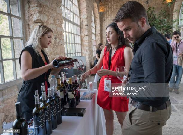 Participants and speakers taste wine during a gettogether in Forte da Cruz at the end of the second day of MUST Fermenting Ideas Wine Summit 2017 on...