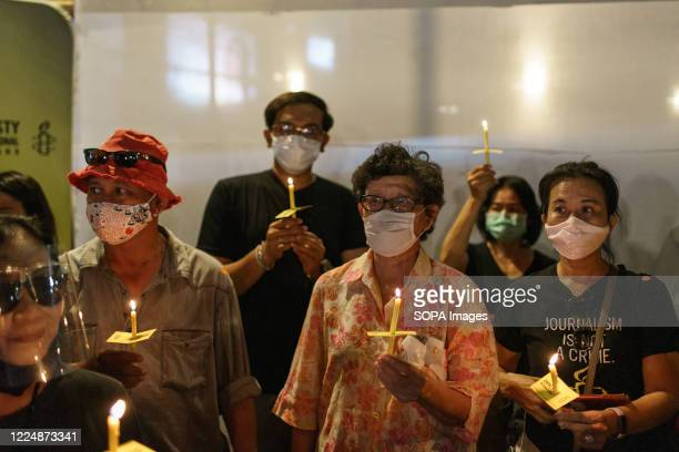 Participants are seen holding lit candles during the one month abduction anniversary of Wanchalearm Satsaksit. People participated in a one month...