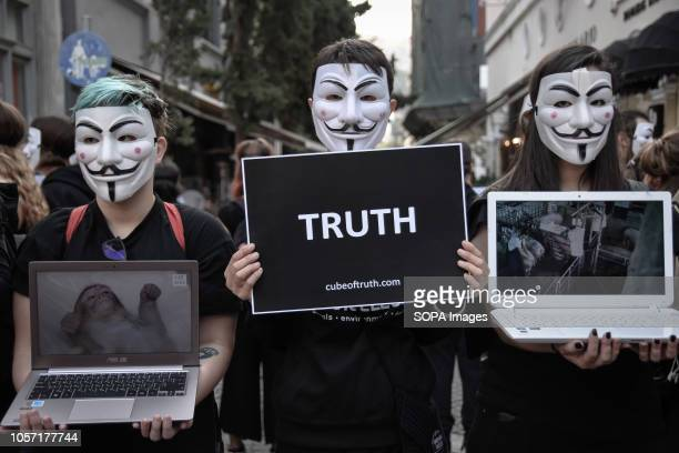Participants are seen wearing anonymous masks while holding placards and laptops during the protest Anonymous is a vegan activists group wearing...