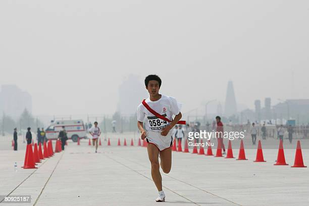 Participants are shrouded with smog as they take part in the long-distance race outside the National Stadium, also known as the 'Bird's Nest' on...
