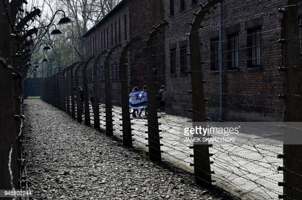 TOPSHOT Participants are wrapped into an Israeli flag as they arrive to the memorial site of the AuschwitzBirkenau Nazi death camp in Oswiecim on...
