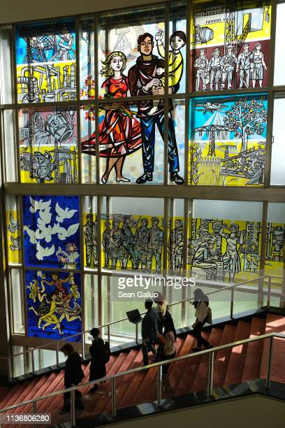 Participants at the Global Solutions Summit walk down stairs next to a communistera stained glass Socialist Realist mural by artist Walter Womacka at...