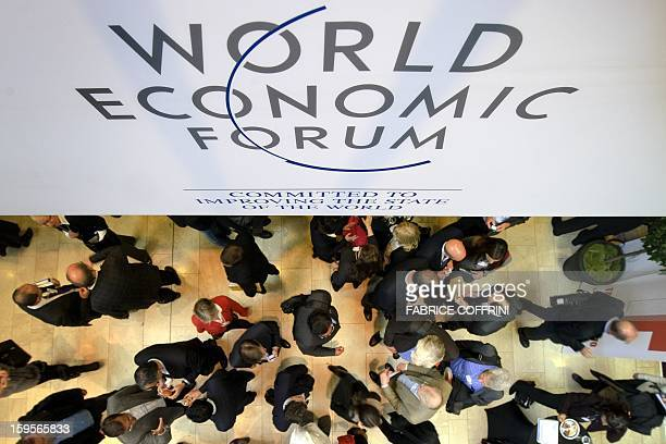 Participants at the World Economic Forum annual meeting chat under a sign on January 25 2012 at the Congress Center in Davos The world's political...