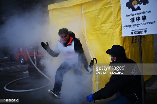 """Participants attend a """"smoke experience"""" to see what it is like to walk through smoke during a """"disaster preparedness drill"""" organised by the Tokyo..."""