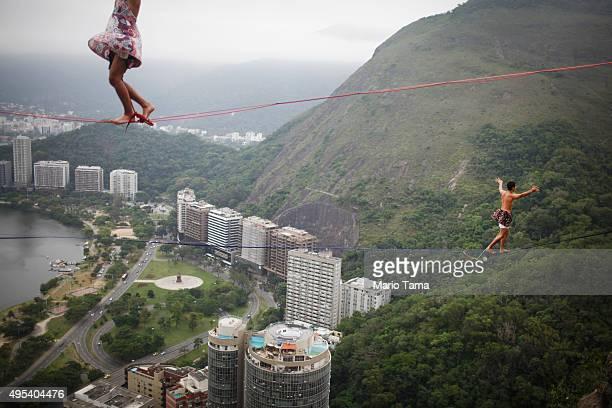 Participants balance on slacklines set up between rocks in the Cantagalo favela community during the Highgirls Brasil festival on November 2 2015 in...