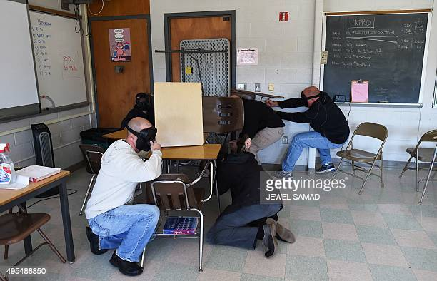 """Participants barricade a door of a classroom to block an """"active shooter"""" during ALICE training at the Harry S. Truman High School in Levittown,..."""