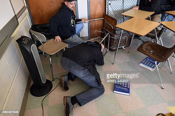 Participants barricade a door of a classroom to block an 'active shooter' during ALICE training at the Harry S Truman High School in Levittown...