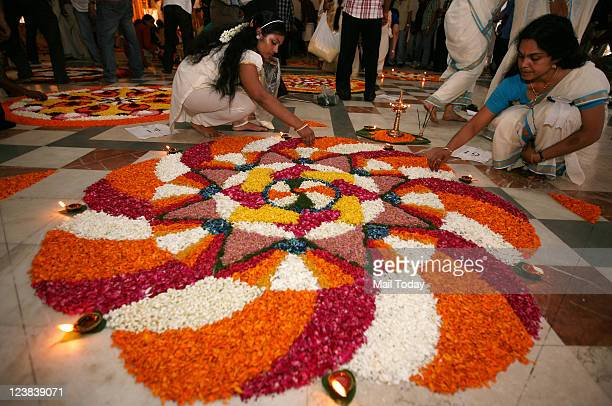 Participants busy in decorating their 'Pookalam' during a contest as part of Onam celebrations organised by Malyalam Manorama newspaper in New Delhi...