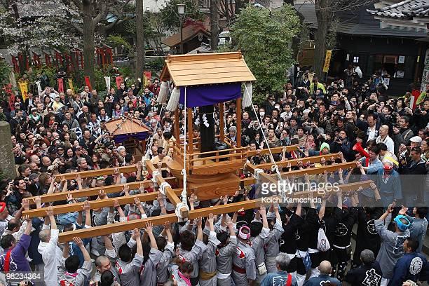 Participants carry a portable shrine with a large gleam black phallus during the Kanamara Festival or the Utamaro Festival near Wakamiya Hachimangu...