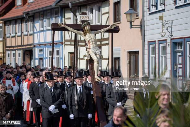 Participants carry an effigy of Jesus Christ nailed to the cross during the annual Palm Sunday procession on March 25 2018 in Heiligenstadt Germany...