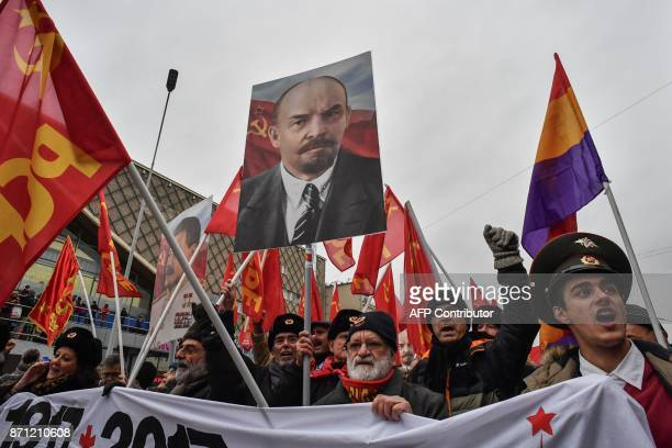 Participants carry red flags and a poster depicting the Soviet Union founder Vladimir Lenin during a rally marking the 100th anniversary of the 1917...