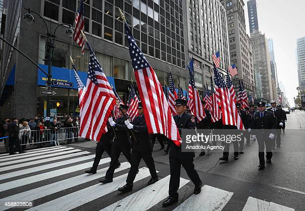 Participants carry US flags as they march during a Veterans Day Parade in New York on November 11 2014