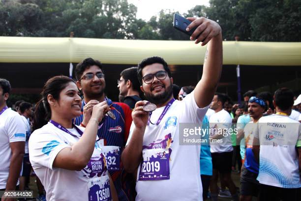 Participants celebrate by Clicking selfie after collecting their medals at Powai Run on January 7 2018 in Mumbai India Of the 14000 participants at...
