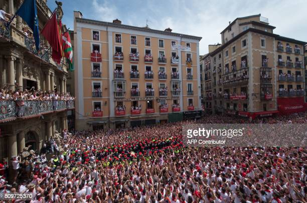 Participants celebrate the 'Chupinazo' to mark the kickoff at noon sharp of the San Fermin Festival in front of the Town Hall of Pamplona northern...