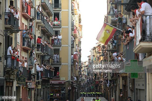 Participants chased by bulls run on the streets through the old town to the bull ring during the San Fermin Running of the Bulls fiesta in Pamplona...