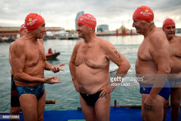Participants chat as they wait for taking part in the 108th edition of the 'Copa Nadal' swimming competition in Barcelona's Port Vell on December 25...