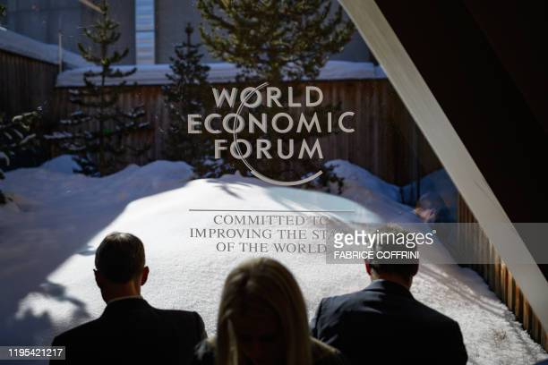 Participants check their messages on electronic devices during the World Economic Forum annual meeting in Davos on January 23 2020