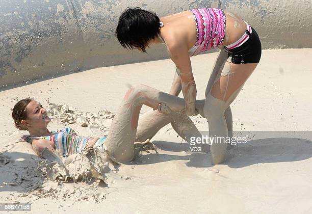 Participants compete during the final of the international women's mud wrestling contest along the East Lake on May 10 2009 in Wuhan of Hubei...