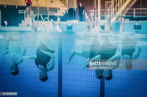 Participants compete in the synchronized swimming contest during the 10th edition of the international Gay Games at the Maurice Thorez swimming pool...
