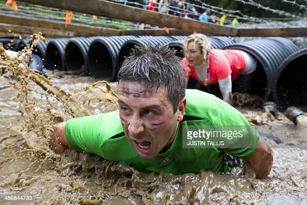 Participants crawl through tubing during the Tough Mudder endurance race in Henley on Thames West of London on April 26 2014 The course is set out...