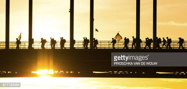 Participants cross a bridge over the Waal river on the first day of the 101st edition of the annual Four Days March of Nijmegen the Netherlands on...