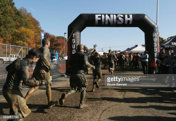 Participants cross the finish line in the Tough Mudder event at Raceway Park on October 20 2012 in Englishtown New Jersey
