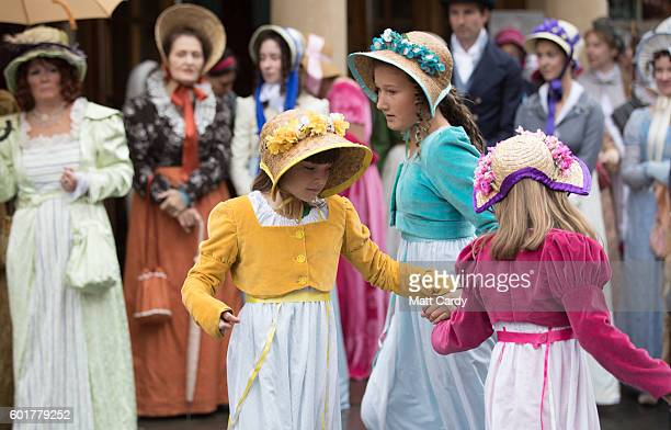 Participants dance as they gather in front of the Assembly Rooms as they prepare to take part in the annual Jane Austen Regency Costumed Parade as it...