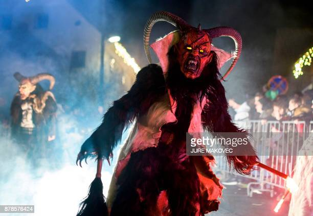 Participants dressed as 'Krampus' creatures parade during 'The Hike of the Krampus of Three Lands' in the centre of Podkoren Slovenia on November 24...