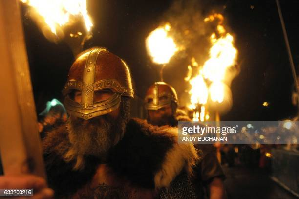 Participants dressed as Vikings carry torches as they march in procession before burning their viking galley ship at the culmination of the annual Up...