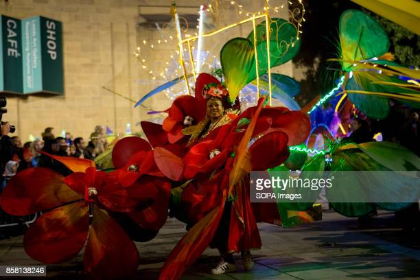 Participants dressed in colourful costume are walking though the street during the Leeds Festival Light Night Leeds is an annual free multiarts and...