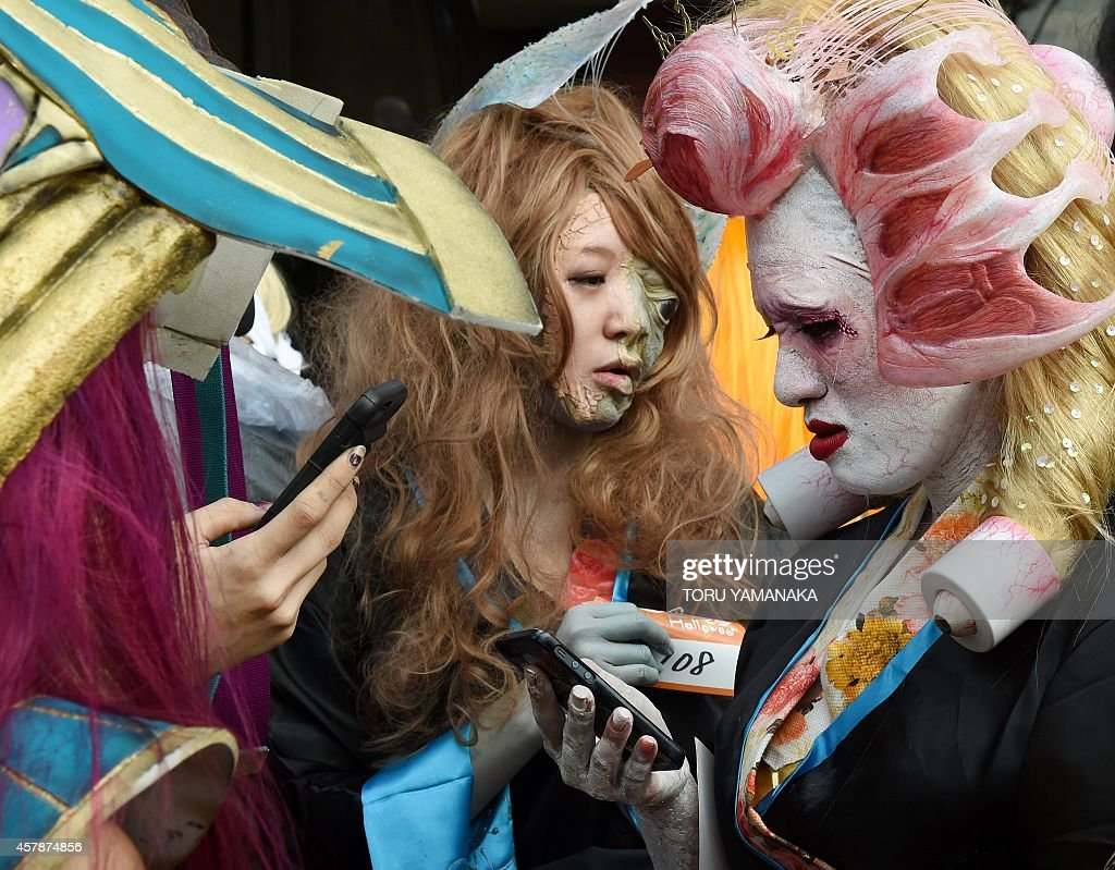 Participants dressed in costumes use their phones as they wait for the Halloween Parade in Kawasaki, a suburb of Tokyo, on October 26, 2014. More than 100,000 visitors watched the street costume parade in which some 2,500 people took part. AFP PHOTO/Toru YAMANAKA