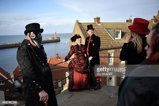 Participants dressed in gothic costumes pose for pictures during the biannual 'Whitby Goth Weekend' festival in Whitby Northern England on November 2...