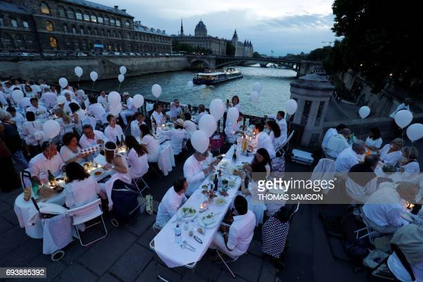 TOPSHOT Participants dressed in white participate in a Diner en Blanc on the Arcole bridge near the City Hall in Paris on June 8 2017 The 29th...