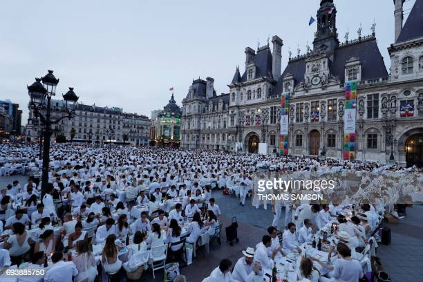 Participants dressed in white participate in a Diner en Blanc outside the City Hall in Paris on June 8 2017 The 29th Edition of the Diner en Blanc...