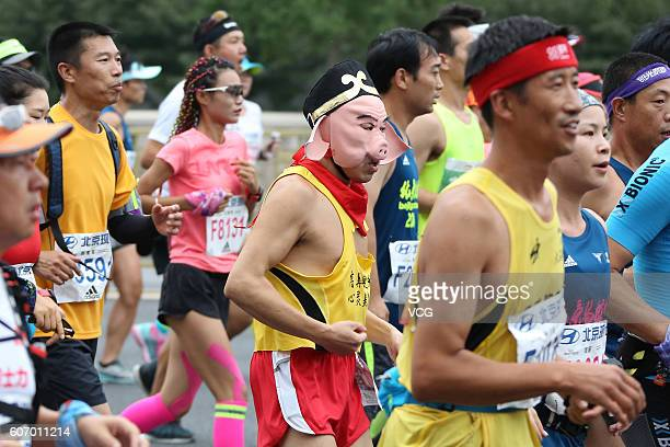 Participants dressed themselves run on road during the 2016 Beijing Marathon on September 17 2016 in Beijing China Running from the Tian'anmen Square...