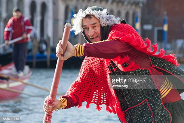 Participants dressed up as elderly women row on the Grand Canal during the 36th Befana Regata